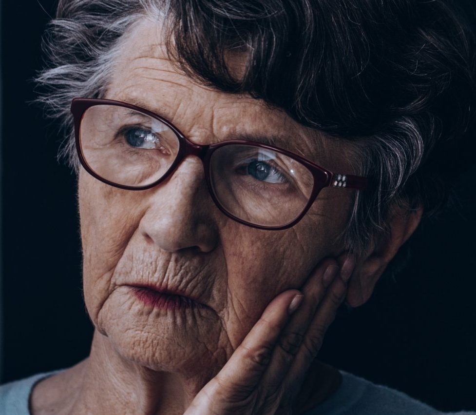 Closeup on an elderly woman's face leaning on her hand as she looks out a window, meaning to signify the isolation of substance abuse in the elderly.