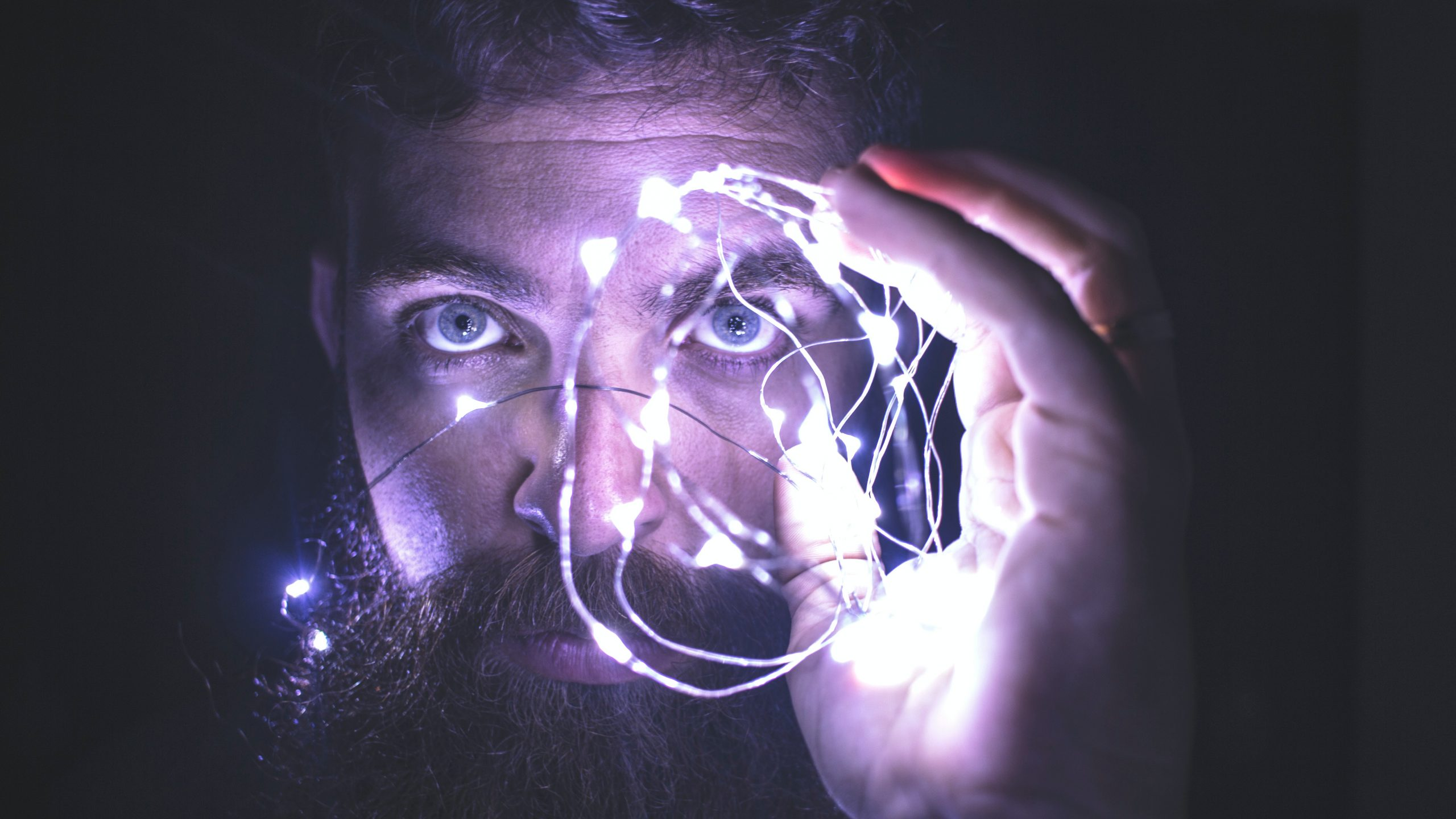 Closeup of a bearded man's face. He eyes are open wide and staring while he holds a cioled string of white lights in front of his left eye. The photo is symbolically representative of meth psychosis.